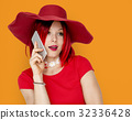 Caucasian Woman in a Red Dress Talking on the Phone 32336428