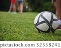 football field, ball on grass, the feet of men 32358241