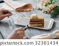 Hands going to eat dessert, yellow mousse cake 32361434