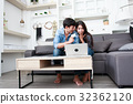 Happy couple online shopping at home 32362120