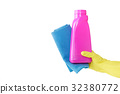 Hand in yellow glove holds pink bottle of liquid 32380772