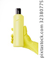 Hand in rubber yellow glove holds a bottle of 32380775