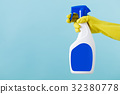Hand in yellow glove holds  spray bottle of liqui 32380778