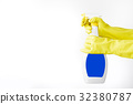 Hand in rubber yellow glove holds  spray bottle o 32380787