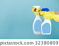 Hand in yellow glove holds  spray bottle of liqui 32380809