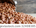 Peanuts in stainless cup on wooden background. 32408385