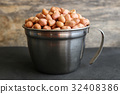 Peanuts in stainless cup on wooden background. 32408386
