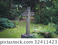 gravestone on / cemetery - stone cross on grave 32411423