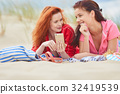 Two young women laying  sunbathing on a white sand beach, relaxi 32419539