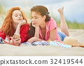 Two young women laying  sunbathing on a white sand beach, relaxi 32419544