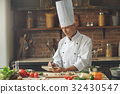 Mature man professional chef cooking meal indoors 32430547