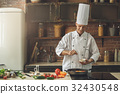 Mature man professional chef cooking meal indoors 32430548