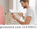 Young man does apartment repairment himself 32430631