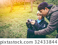 Father teaching his son photographing outdoors. 32433844