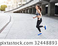Happy young woman training with jumping-rope 32448893
