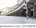 Joyful girl skipping on rope near stadium 32448896