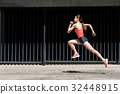 Confident young woman running outdoors 32448915