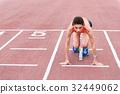 Confident girl posing in blocks to start running 32449062