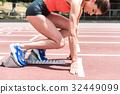 Confident female sprinter standing at starting 32449099