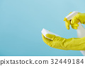 Hand in yellow glove holds spray bottle of liquid 32449184