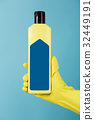 Hand in rubber yellow glove holds a bottle of 32449191
