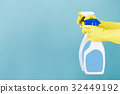 Hand in yellow glove holds  spray bottle of liqui 32449192