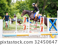 Young rider girl training jumping with her trainer 32450647