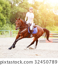 Young girl on horse at show jumping competition 32450789