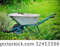 Old wheelbarrow on a green grass field background 32453566