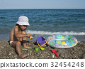 girl plays with toys on the beach 32454248