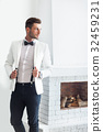 Handsome stylish man in elegant suit standing near fireplace 32459231