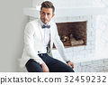 Handsome stylish man in elegant suit sitting near fireplace 32459232
