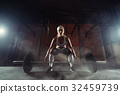 Muscular young fitness woman lifting a weight in 32459739