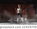 Muscular young fitness woman lifting a weight in 32459749