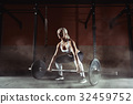 Muscular young fitness woman lifting a weight in 32459752