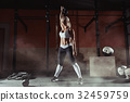 Muscular young fitness woman lifting a weight in 32459759