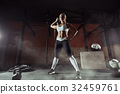 Muscular young fitness woman lifting a weight in 32459761
