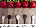 Conceptual image of make-up brushes next to roses 32459765