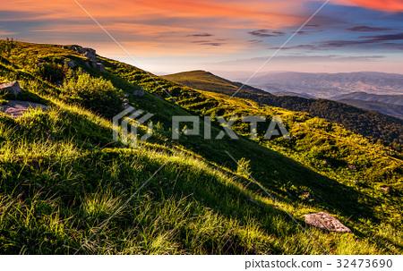 mountain ridge with peak behind hillside at sunset 32473690