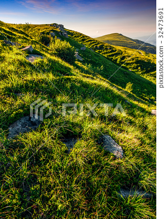 mountain ridge with peak behind hillside at sunset 32473691