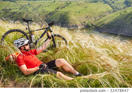Cyclist in Red Jacket and Helmet Resting near 32478647