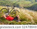 Cyclist in Red Jacket and Helmet Resting near 32478649