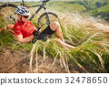 Cyclist in Red Jacket and Helmet Resting near 32478650