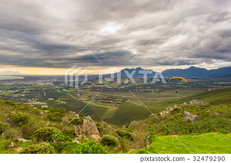 Paraglider flying over the green mountains 32479290
