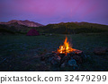 Tent and burning camp fire at dusk on the mountain 32479299