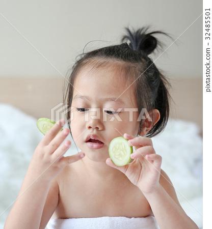 Child girl holding cucumber slices 32485501