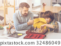 Positive nice father and son playing chess 32486049