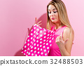 Young woman holding a shopping bag  32488503