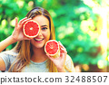 Happy young woman holding grapefruit 32488507