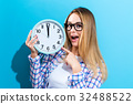 Woman holding clock showing nearly 12 32488522